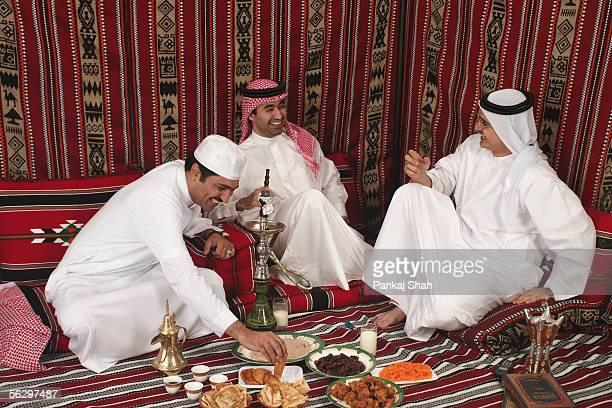 arab men eating their meal - majlis stock pictures, royalty-free photos & images