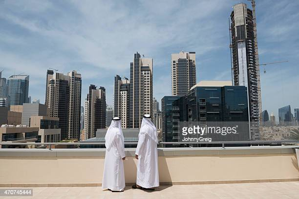 Arab men look at Middle East real estate
