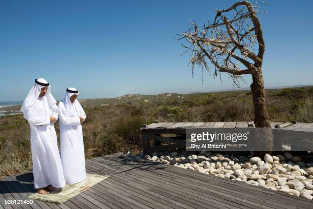Arab men praying on boardwalk.
