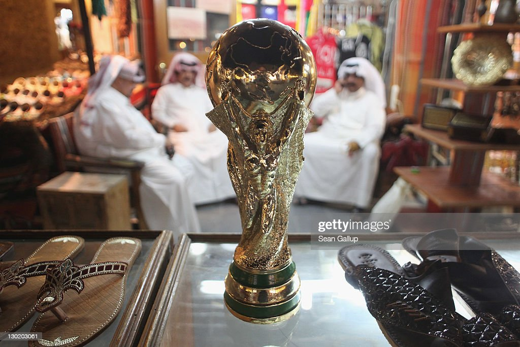 Arab men sit at a shoemaker's stall with a replica of the FIFA World Cup trophy in the Souq Waqif traditional market on October 24, 2011 in Doha, Qatar. Qatar will host the 2022 FIFA World Cup football competition and is slated to tackle a variety of infrastructure projects, including the construction of new stadiums.