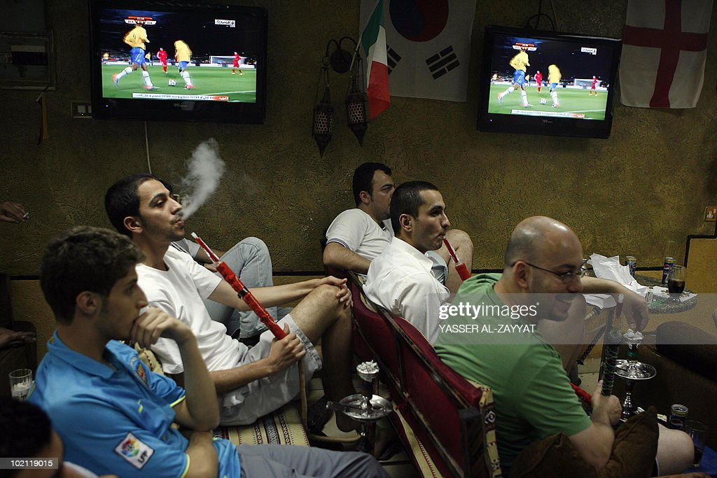 Arab men smoke waterpipe as they watch the 2010 World Cup football match between Brazil and North Korea at a coffee shop in Kuwait City of on June 15, 2010.