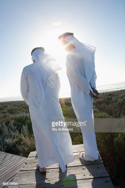 arab men standing on boardwalk. - arab old man stock pictures, royalty-free photos & images