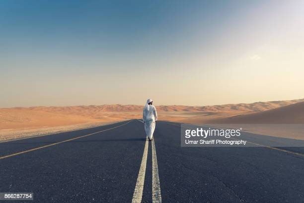arab men with traditional dress in uae desert - uae heritage stock photos and pictures