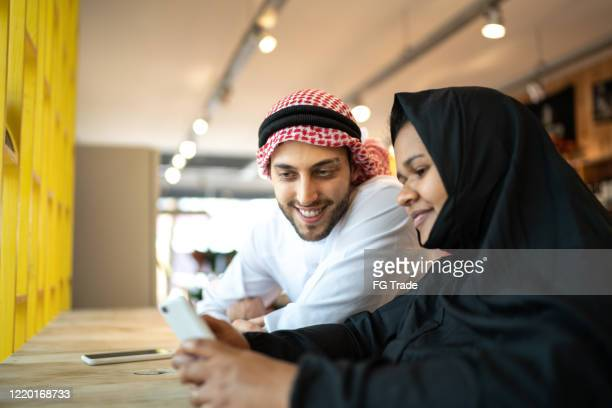arab middle east couple doing a video call on mobile phone at coffee shop - united arab emirates stock pictures, royalty-free photos & images