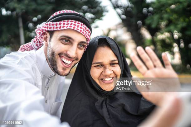 arab middle east couple doing a video call on mobile phone at street - video still stock pictures, royalty-free photos & images