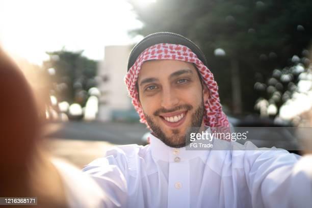 homem árabe do oriente médio tirando uma selfie na rua - qatar - fotografias e filmes do acervo