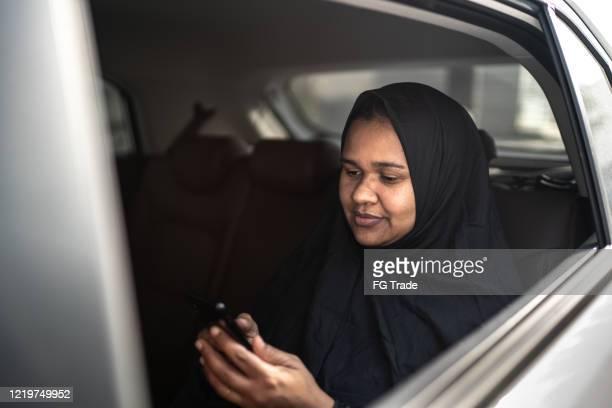 donna del medio oriente araba che usa il cellulare in auto - qatar foto e immagini stock