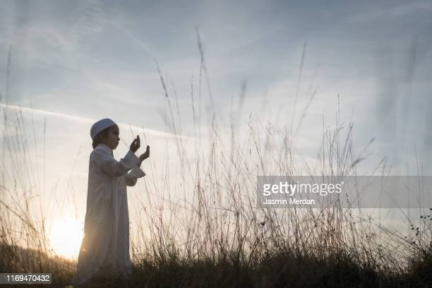 arab muslim child praying on sunset meadow - beautiful ramadan stock pictures, royalty-free photos & images