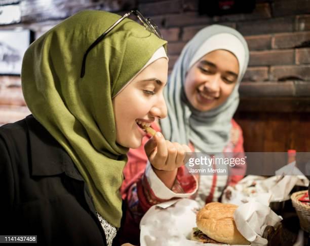 arab muslim girls eating burger - jordanian workforce stock pictures, royalty-free photos & images