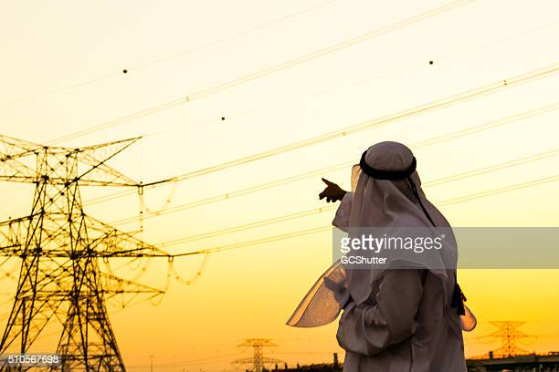 arab pointing towards electrical pylon - power supply stock pictures, royalty-free photos & images