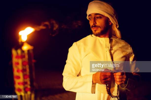 arab standing next to an oil lamp with prayer beads - kaffiyeh stock pictures, royalty-free photos & images