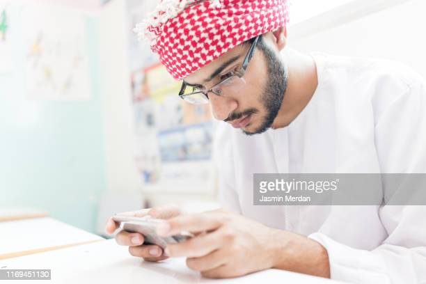 arab student using phone in class - jordanian workforce stock pictures, royalty-free photos & images