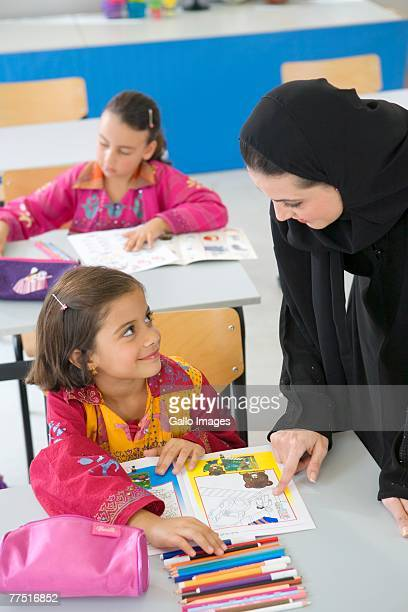 Arab Teacher Looking Down at Student at a Desk in a Classroom, Elevated View. Dubai, United Arab Emirates