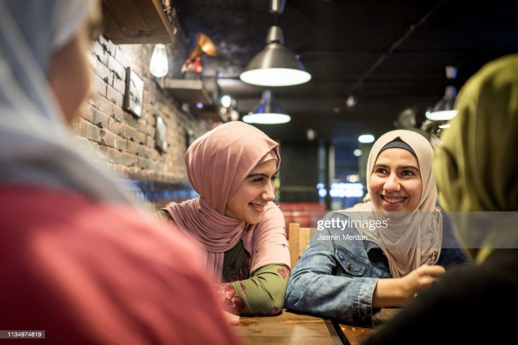 Arab teenage girls having fun together in restaurant : ストックフォト