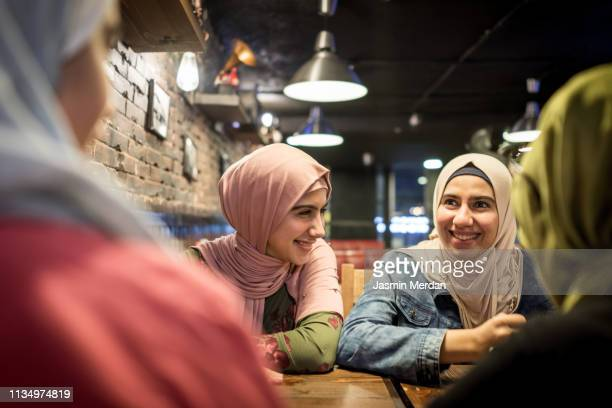 arab teenage girls having fun together in restaurant - middle east stock pictures, royalty-free photos & images