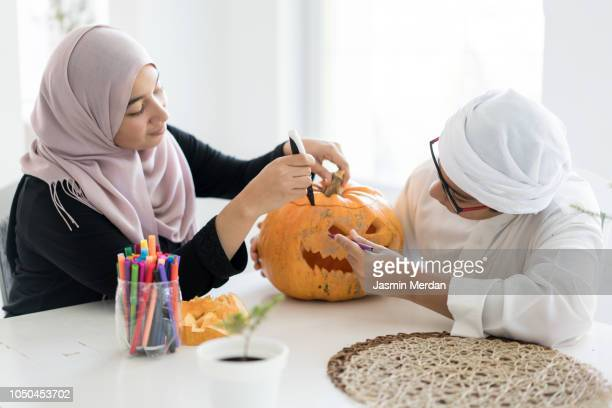 arab teenagers with halloween pumpkin lantern - carving craft product stock pictures, royalty-free photos & images