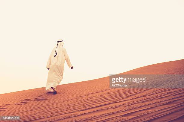 Arab walking alone on the sand dunes