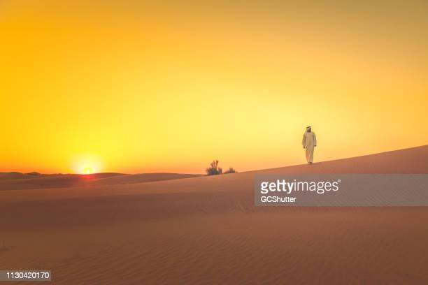 arab walking on the sand dunes at distant during sunset - social history stock pictures, royalty-free photos & images