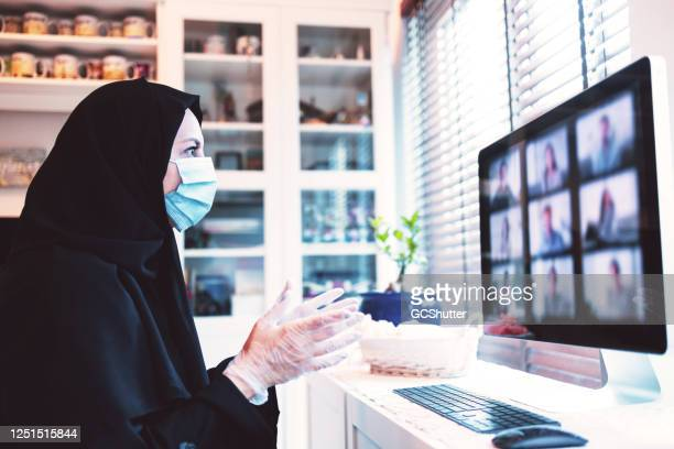 arab woman attending video call while working from home - covid-19 series - hand sign stock pictures, royalty-free photos & images