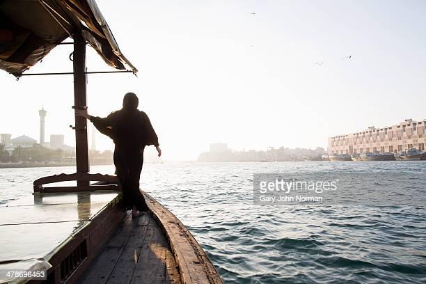 arab woman crossing Dubai Creek on a boat
