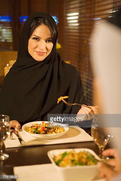Arab woman dining with husband in restaurant. United Arab Emirates