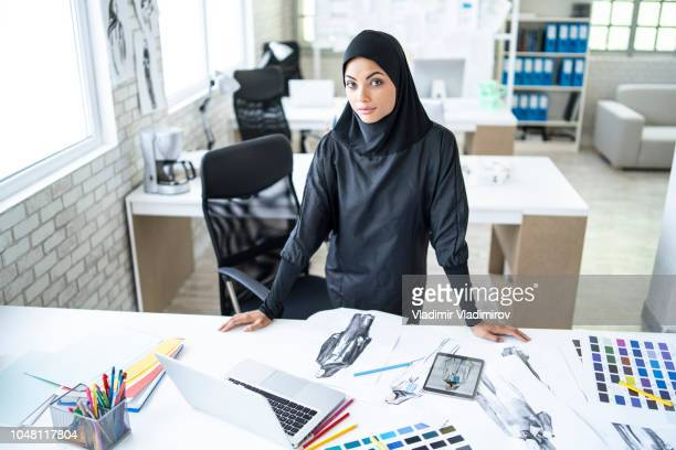 Arab woman fashion designer standing in studio