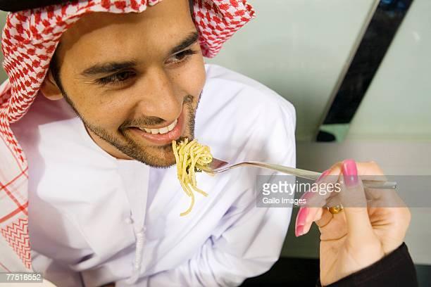 Arab Woman Feeds Smiling Husband Spaghetti, High Angle View. Dubai, United Arab Emirates