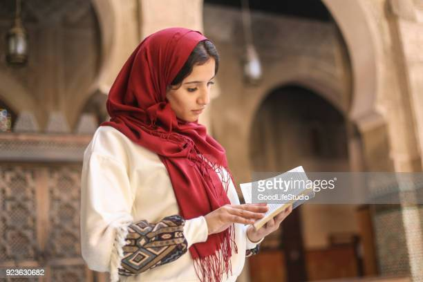 arab woman reading a book - holy quran stock pictures, royalty-free photos & images