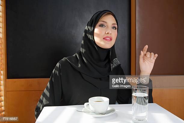Arab Woman Signalling for Service in restaurant. Dubai, United Arab Emirates