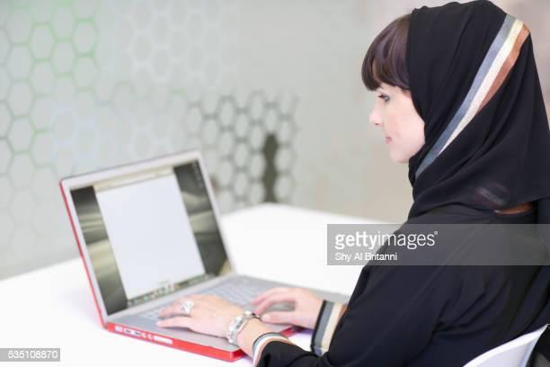 Arab woman using laptop in office.