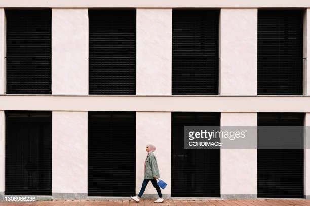 arab woman walking outdoors on the street. - emigration and immigration stock pictures, royalty-free photos & images