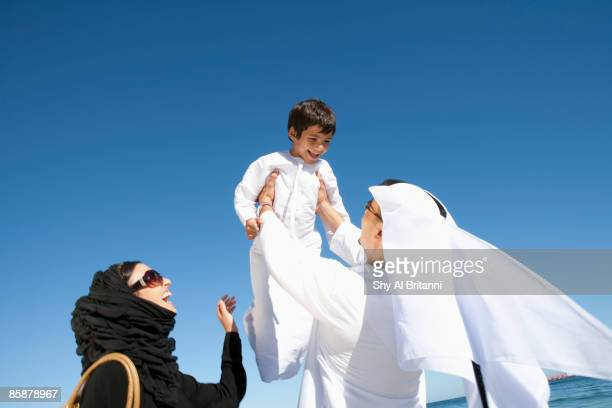 arab woman watching man lifting boy. - arab family stock pictures, royalty-free photos & images