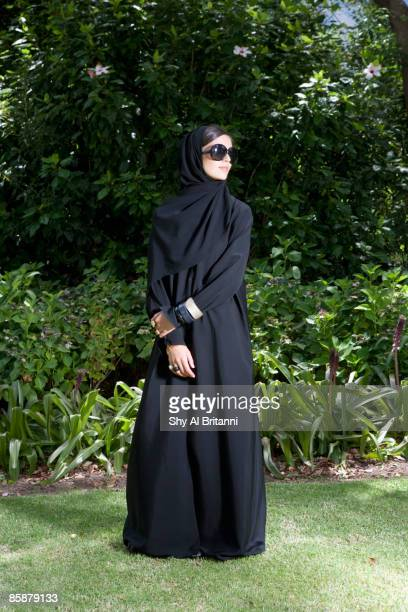 arab woman wearing sunglasses standing in park. - looking away stock pictures, royalty-free photos & images