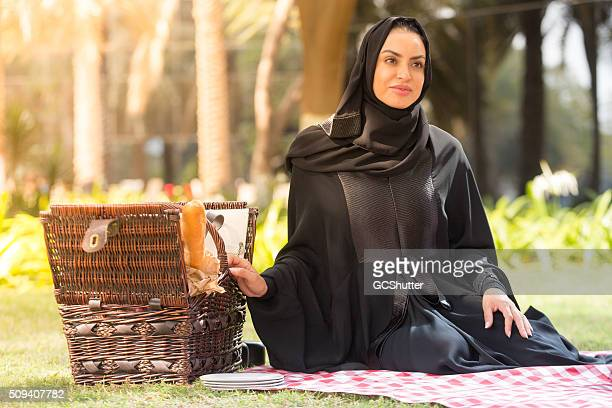 Arab woman with a picnic basket in a park, Dubai