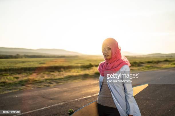 Arab woman with hijab holding skateboard