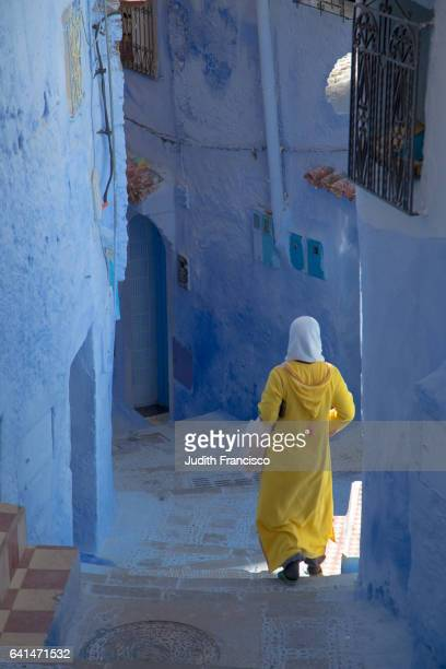 arab woman with yellow dress downstair blue town of chaouen in morocco - chefchaouen photos et images de collection