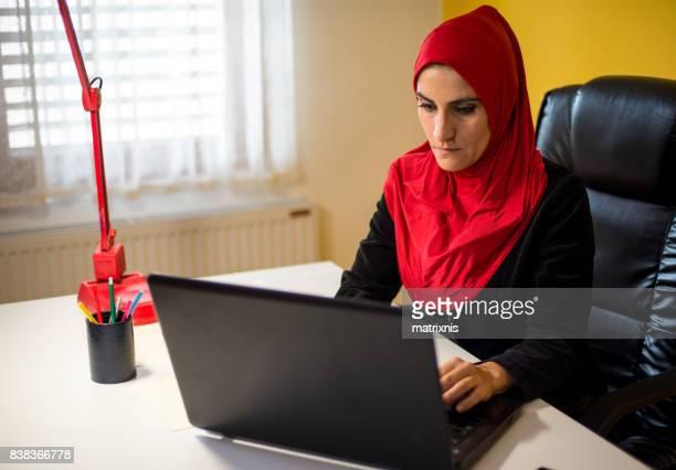 Arabische Frau mit Laptop zuhause arbeiten.