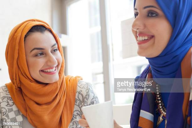 arab women chatting at café.  - modest clothing stock pictures, royalty-free photos & images