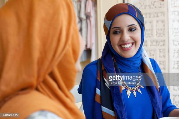 arab women chatting in boutique.   - business finance and industry stock pictures, royalty-free photos & images