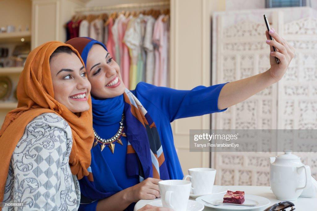 Arab women taking selfie in boutique. : Stock Photo
