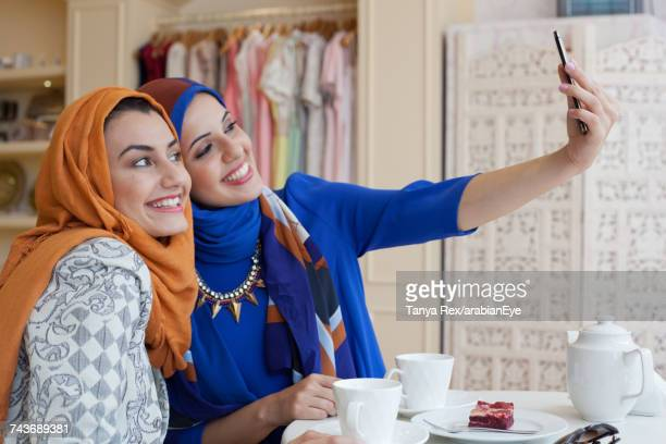 Arab women taking selfie in boutique.