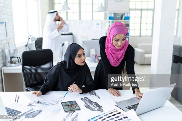 arab women working together in modern workplace - middle east stock pictures, royalty-free photos & images