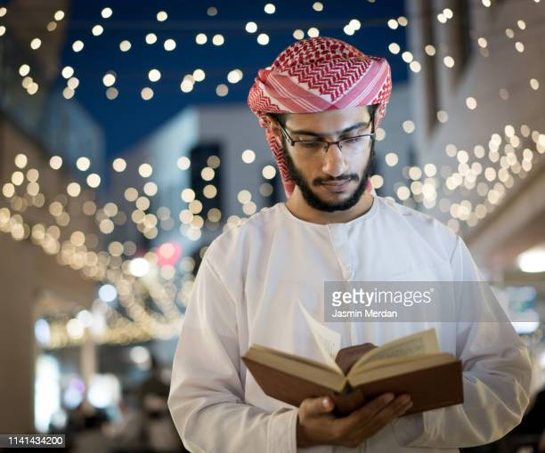 arab young adult reading book - kaffiyeh stock pictures, royalty-free photos & images