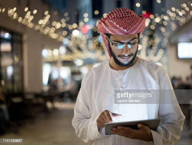 arab young man with tablet outdoors - qatar fotografías e imágenes de stock