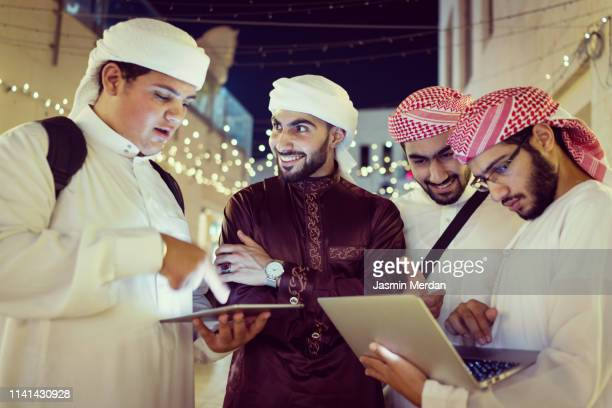arab young men with laptop on night street - gulf countries stock pictures, royalty-free photos & images