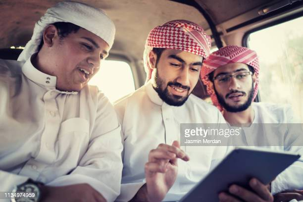 arab young traditional men in car using tablet - arabia stock pictures, royalty-free photos & images