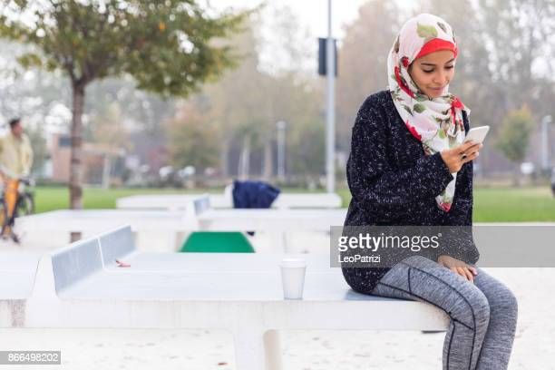 arab youth - millennial texting on mobile while waiting for a friend at the public park - moroccan culture stock photos and pictures