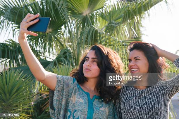 arab youth; two young women make a selfie - moroccan girls stock photos and pictures
