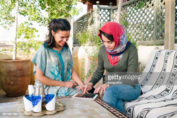 arab youth: two young women sitting together drinking tea - moroccan girls stock photos and pictures