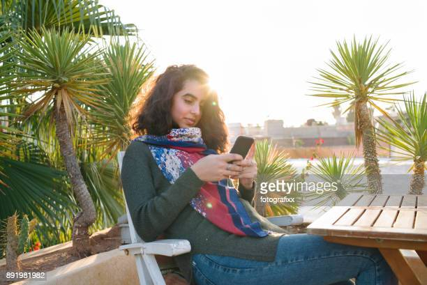 arab youth: young moroccan woman looking at smart phone - moroccan girls stock photos and pictures